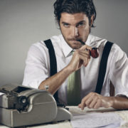 Image of a freelance editor sitting in at a typewriter.