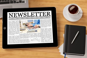 Shows a company newsletter on a tablet device. Writing a company newsletter can boost your company's image.