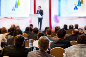 Shows a speaker at the front of an audience. Event promotion is an important part of organising a successful event.