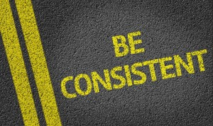 "Proofreading for consistency. Shows bright yellow text on a road ""Be Consistent""."
