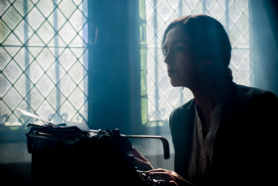 Image of a woman in a dark room at a typewriter looking like a ghostwriter